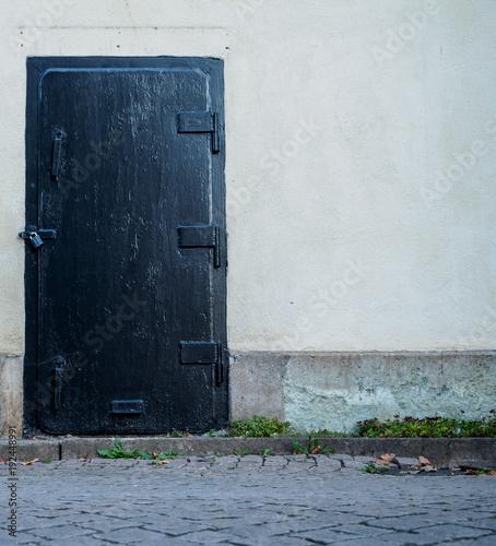 black iron door on beige house