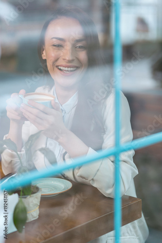 Sincere person. Cheerful gay good looking woman drinking coffee while laughing and posing at the table