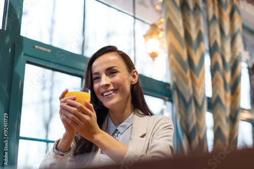 Source of vitamins. Young pleasant cute woman posing near window while grinning and carrying glass with juice