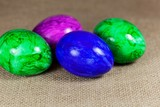 Colored Easter eggs on a brown textile background - 192454309