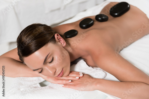 beautiful young woman having hot stones massage in spa salon - 192456725