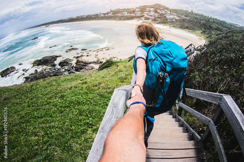 Foto Murales Couple summer vacation travel. Woman walking on romantic honeymoon promenade holidays holding hand of husband following her, view from behind