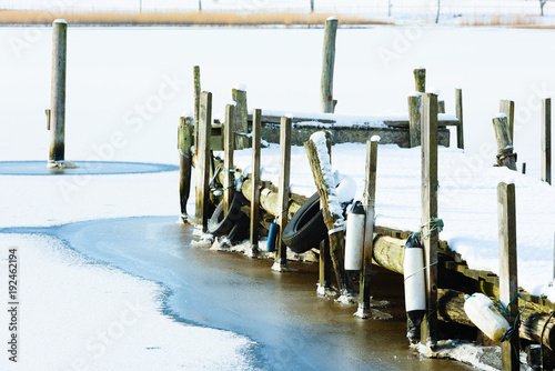 Old wooden pier in ice and snow. Mooring poles along the side and out in the sea. Opposite shore visible across the bay.