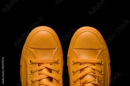 Yellow sneakers on a black background. Fashionable sneakers of yellow color against a dark background.