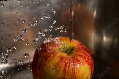 Foto Murales washing apples with splashes of water and lots of waterdrops on a steel background