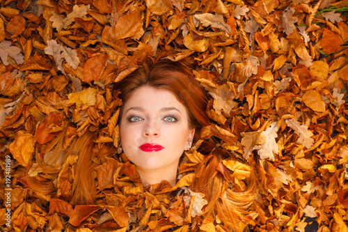 Young woman covered by leaves.