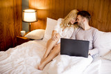 Loving couple surfing internet on the bed in bedroom