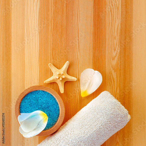 Foto op Canvas Spa Bowl with scrub, petals, starfish and towel. Wooden background. Copy space.