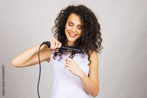 Papiers peints Salon de coiffure beautiful hair model girl young adult with curly hair and hair iron straightener happy and unhappy concept