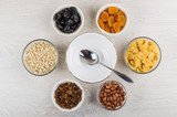 Empty bowl, spoon and different ingredients for preparation muesli - 192487940
