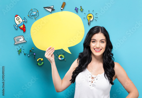 Wall mural Young woman holding a yellow speech bubble