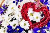 beautiful wicker heart on a background of flowers - 192495763