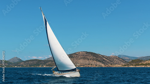 Fotobehang Zeilen Yacht boat with white sails in the Sea near the coasts of the Islands.