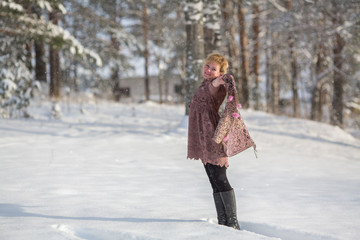 Young russian woman posing in a snowy park in winter.