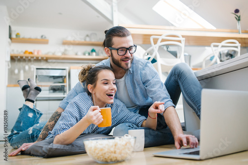 Young couple watching movie on laptop at home