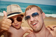 Father and son are taking a selfie photo while having a rest on the beach.