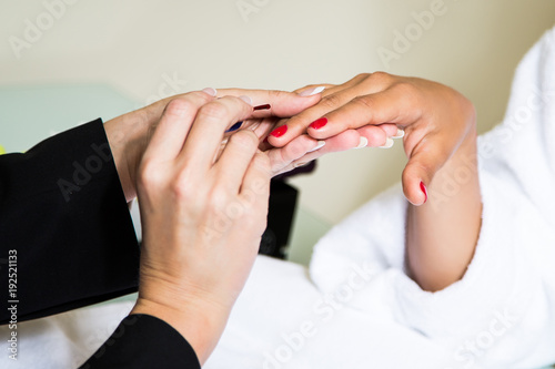Fotobehang Manicure мастер маникюра делает клиентке в белом халате красный маникюр лаком