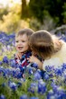 Two adorable small children in a field of Texas Bluebonnets