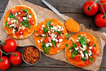 Spicy hummus mini flat breads with tomatoes and feta. Above scene with on a rustic wood background. Healthy eating concept.