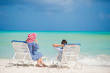 Happy family relaxing on a tropical beach on the beach chairs