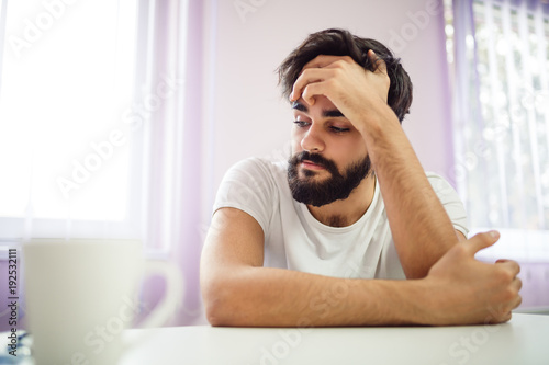 Close-up of young depressed sad man with medical problems. Handsome man talking with his doctor.