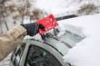 Cleaning snowy car in winter