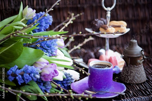 a bouquet of spring flowers in lilac tones and a cup of coffee with cakes