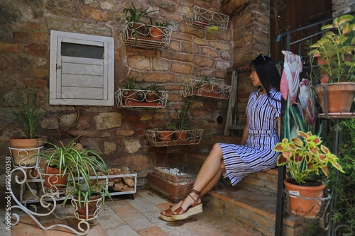 Deurstickers Toscane An Asian woman siting at a stairs with green plant around in Tuscany, Italy