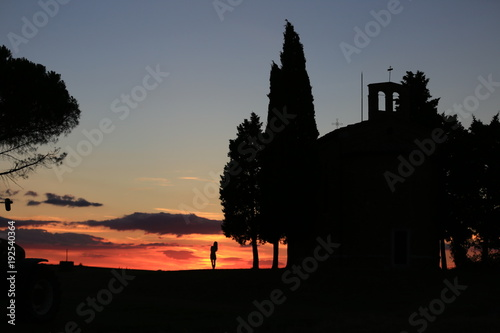 Papiers peints Toscane silhouette of a woman standing next to a church under sunset in Tuscany , Italy