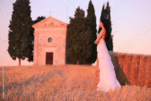 Fotobehang Koraal An Asian woman in white dress standing in front of a small church in Tuscany , Italy under sunset