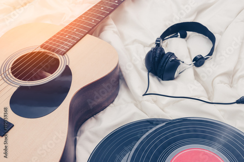acoustic guitar, record & headphone on white bed. music background