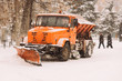 the snowplow stands on the street during the day