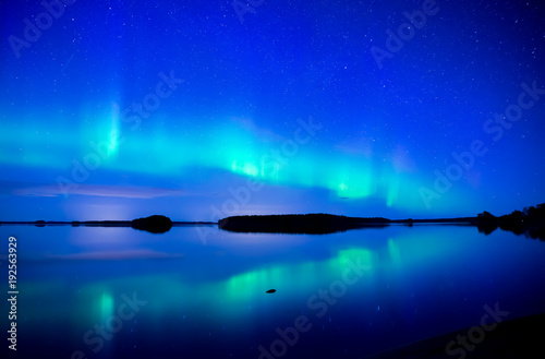 Fotobehang Donkerblauw Northern lights dancing over calm lake. Farnebofjarden national park in Sweden
