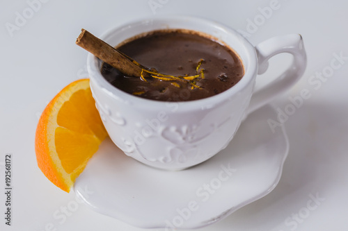Delicious hot chocolate with orange on a white table.