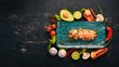 Tiger prawns on an avocado pillow and fresh vegetables. Top view. On a black wooden background. Copy space.