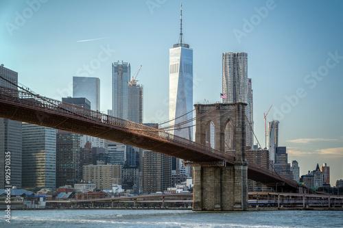 Foto Murales Lower Manhattan Panoramic Skyline and Brooklyn Bridge, New York during sunset. Spotlight on the bridge.