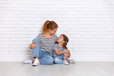 happy family mother and child daughter near an empty wall - 192571537