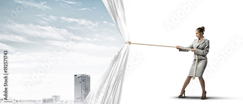 Young woman opening white curtain and presenting modern city landscape