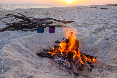 Plexiglas Lavendel Two mugs stand next to bonfire during sunset on the sea