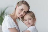 close-up portrait of mother and daughter embracing and looking at camera - 192578935