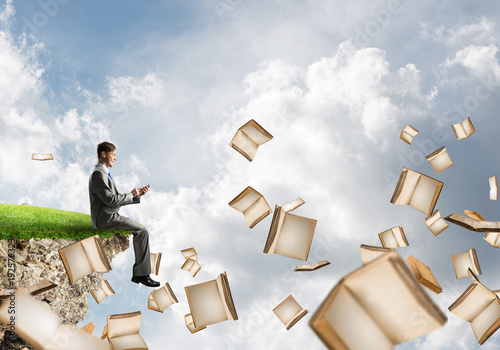 Man using smarphone and many books flying in air