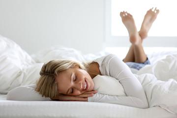 Hübsch blonde frau liegt auf einem Bett