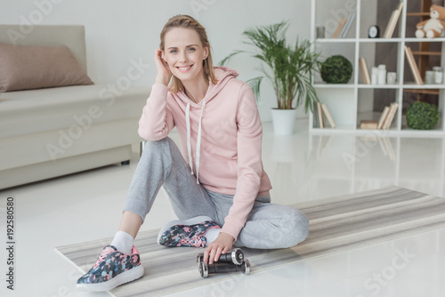 attractive woman sitting on yoga mat with dumbbells at home