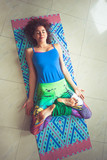 young woman lying on mat with legs in lotus position indoor shot from above - 192581308