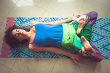 young woman lying on mat with legs in lotus position indoor shot from above - 192582347