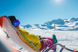 Photo of sporty woman in helmet sitting at snowy resort - 192583960