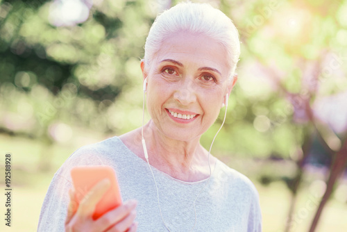 Modern life. Close up of optimistic elderly woman using mobile phone while listening to music and expressing cheer