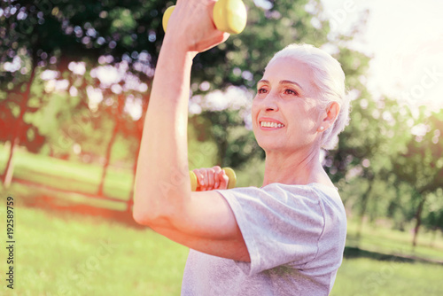Always in fit. Close up of cheerful elderly woman looking away while training with weights
