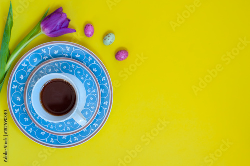 A floral blue tea set on yellow background with chocolate ehhs and a tulip flower. Flat-lay. Negative space.