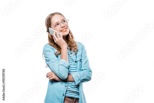 happy teenage girl in eyeglasses talking by smartphone and looking away isolated on white